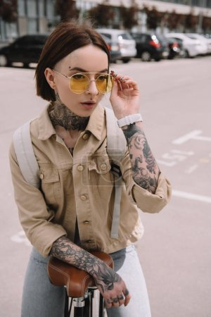 attractive stylish tattooed woman standing with bicycle at street