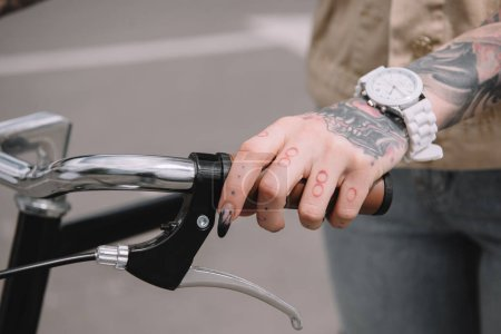 cropped image of female tattooed hand with wristwatch