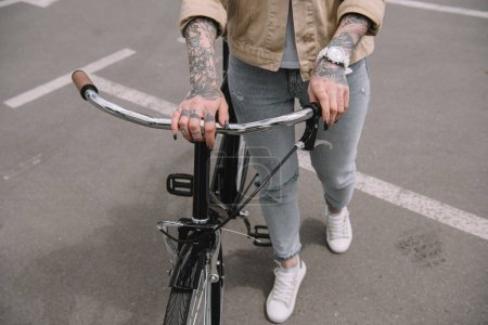 cropped image of tattooed woman standing with bicycle at parking lot