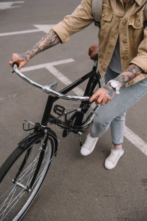 partial view of tattooed woman standing with bicycle at parking lot