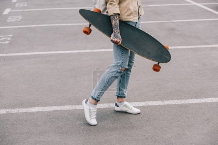 cropped image of stylish tattooed woman holding longboard at parking lot