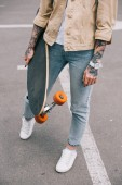 cropped image of stylish tattooed woman holding skateboard at parking lot