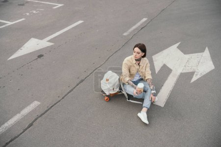 high angle view of tattooed woman sitting on skateboard with coffee cup at parking lot