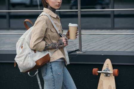 Photo for Cropped image of tattooed woman with backpack holding coffee cup and standing near skateboard at street - Royalty Free Image