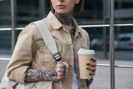 Foto de Recortar imagen de la mujer tatuada con estilo con mochila con papel taza de café - Imagen libre de derechos