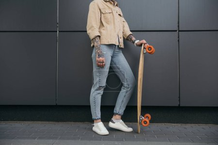 partial view of stylish tattooed woman standing with skateboard against black wall