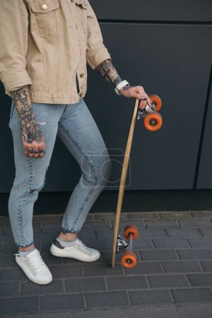 cropped image of tattooed woman standing with skateboard against black wall
