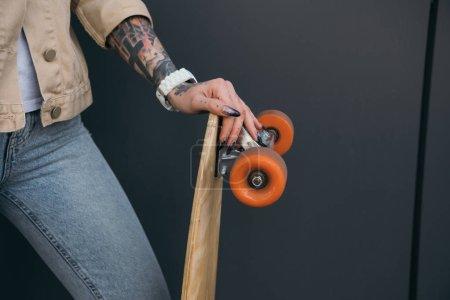 cropped image of tattooed woman holding skateboard near black wall