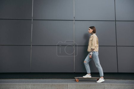 side view of tattooed woman standing with skateboard against black wall