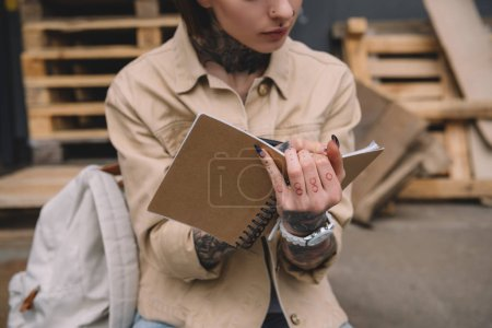 cropped image of tattooed woman writing in textbook