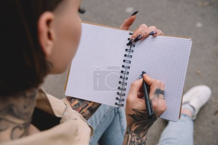 Photo for Selective focus of tattooed young woman writing in empty textbook - Royalty Free Image