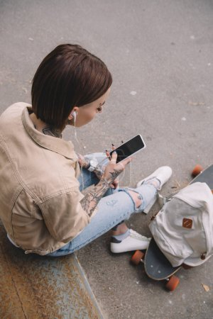 high angle view of tattooed woman in earphones listening music with smartphone near skateboard and backpack