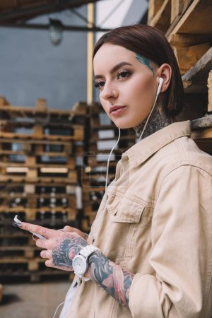 young tattooed woman in earphones listening music with smartphone