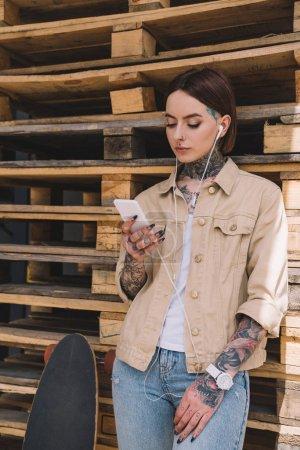 femme élégante tatouée écouteurs écoute la musique avec smartphone près de skateboard
