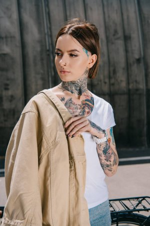 portrait of tattooed woman with jacket on shoulder looking away