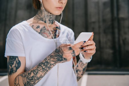 cropped image of tattooed woman in earphones listening music with smartphone