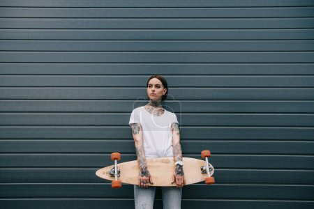 attractive young woman with tattoos holding skateboard against black wall