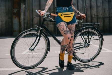 cropped image of stylish tattooed girl with waist bagstanding with bicycle at street