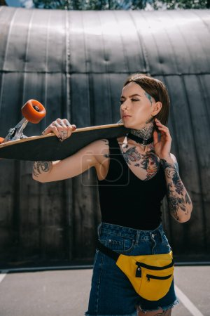 young stylish tattooed girl looking away and holding skateboard over shoulder