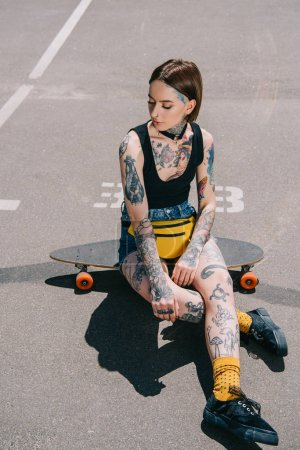 stylish young woman with tattoos sitting on skateboard at parking lot