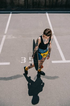 high angle view of stylish tattooed girl holding skateboard at parking lot