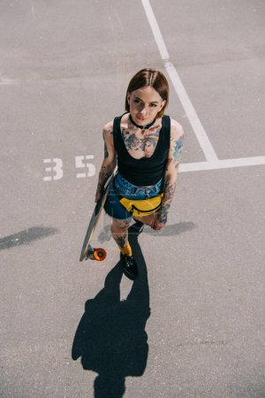 high angle view of stylish tattooed girl holding skateboard and looking at camera at parking lot
