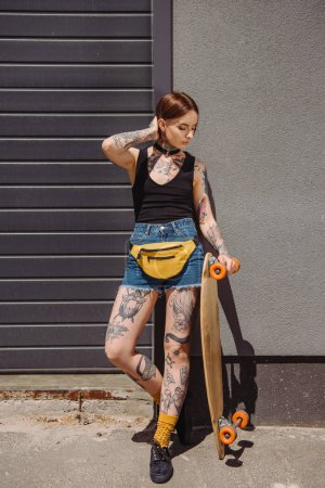 attractive stylish tattooed girl standing with skateboard at street