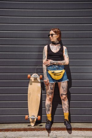 stylish girl with tattoos in sunglasses looking away and standing near skateboard at street