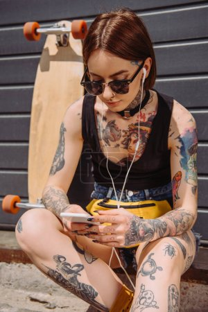 young tattooed woman in earphones listening music with smartphone near skateboard