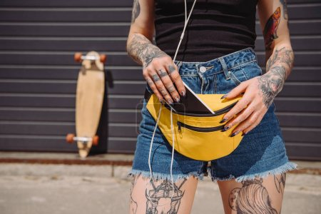 cropped image of tattooed girl putting smartphone with blank screen in waist bag