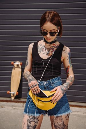 stylish tattooed woman listening music in earphones and putting smartphone in waist bag
