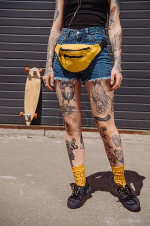 cropped image of stylish tattooed woman with waist bag