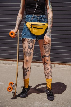 cropped image of stylish tattooed woman standing with skateboard at street