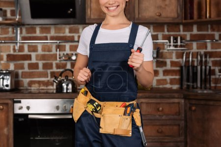 cropped shot of smiling young repairwoman with screwdriver standing at kitchen