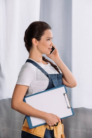 side view of beautiful young repairwoman with clipboard talking by phone