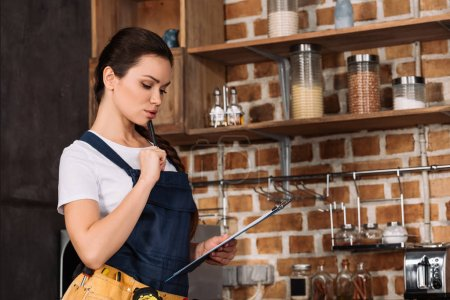 thoughtful young repairwoman with clipboard standing at kitchen