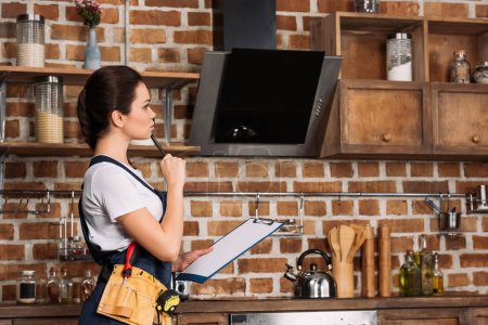 thoughtful young repairwoman with clipboard standing at kitchen and looking away