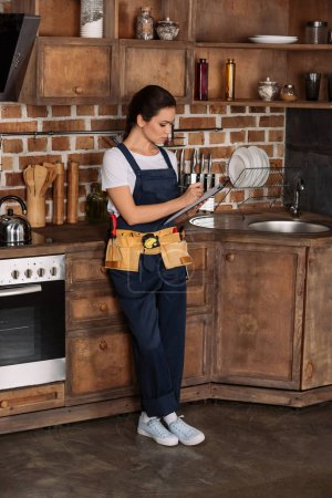 confident young repairwoman writing in clipboard while standing at kitchen