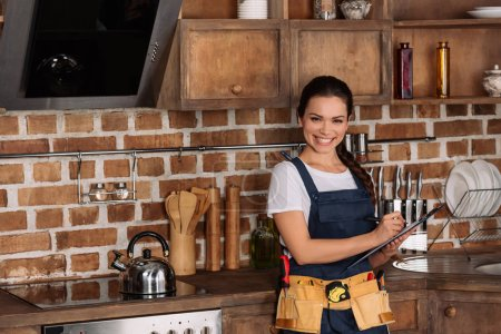 beautiful young repairwoman with clipboard standing at kitchen and looking at camera