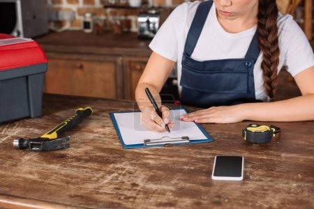 cropped shot of young repairwoman in overall writing in clipboard at kitchen
