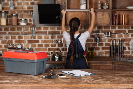 various tools lying on kitchen table with blurred young repairwoman measuring cabinet on background