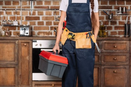 Photo for Cropped shot of repairwoman with toolbox and toolbelt standing at kitchen - Royalty Free Image