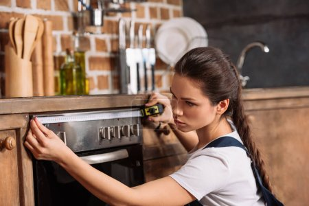 Serious young repairwoman measuring width of oven...