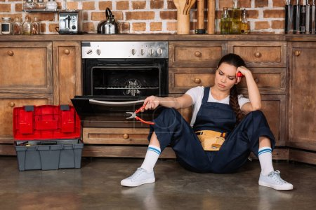 exhausted young repairwoman sitting on floor at kitchen