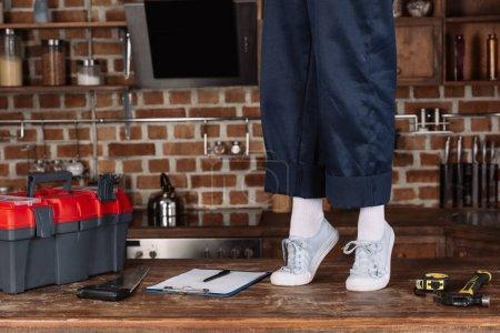 Photo pour Plan recadré de réparatrice en pantalon de travail et chaussures blanches debout sur les orteils sur la table de cuisine - image libre de droit