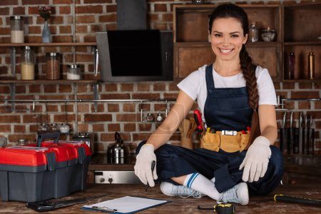 happy young repairwoman sitting on kitchen table with tools and looking at camera