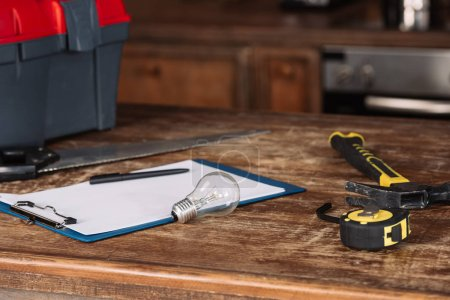 close-up shot of blank clipboard with tools on wooden table