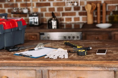 close-up shot of blank clipboard with various tools on wooden table