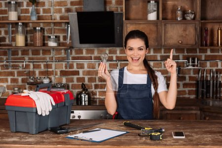 happy young repairwoman with light bulb pointing up and looking at camera