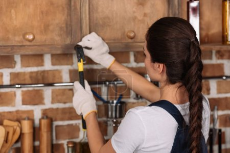 young repairwoman in work gloves hammering nail into kitchen cabinet